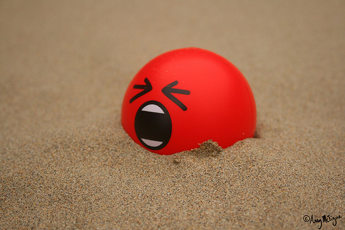 An angry red ball half buried in the sand