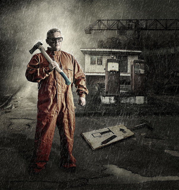 Bespectacled man with an axe at the filling station
