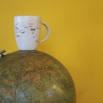 a mug sitting upon a planet floating in yellow space